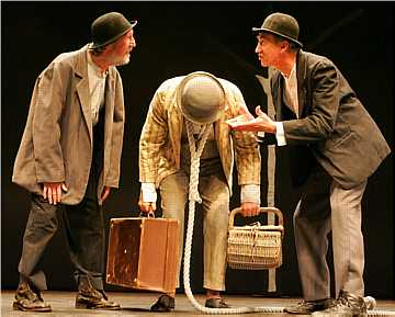 Three characters on stage, two men in bowler hats either side of a man bending under the weight of luggage.