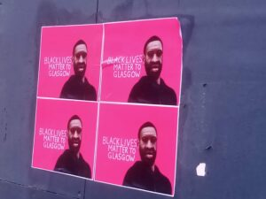 Four identical posters affixed to a wall, depicting George Floyd, and the message, 'Black Lives Matter to Glasgow', white lettering on a pink background, mimicking the style of the city's promotional 'People Make Glasgow' slogan.
