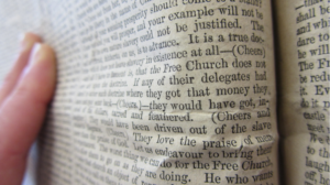 fingers resting on old bound newspaper, partly in focus, pages slightly creased.
