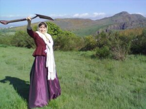 Woman in 19th-century dress brandishing a spade, with Arthur's Seat and Salisbury Crags in the background.